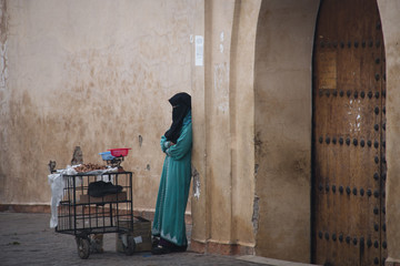 A covered muslim woman on the street of Marrakesh in Morocco