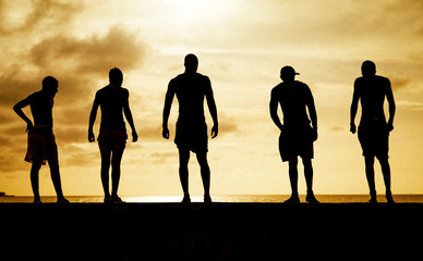 Silhouette of men standing on the beach during sunset
