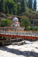 View of the rapid river Parvati near Sightcam a temple and a Gurudwara, Manikaran, Himachal Pradesh, Northern India.