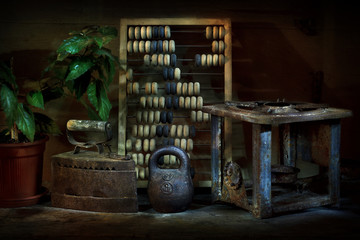 Still life with vintage objects. Iron, scores, weight, primus