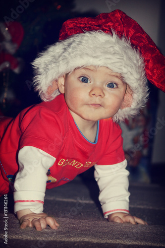 08ab38d16f0 Beautiful smiling baby with big eyes in the cap Santa Claus and red  clothes. A dark background.