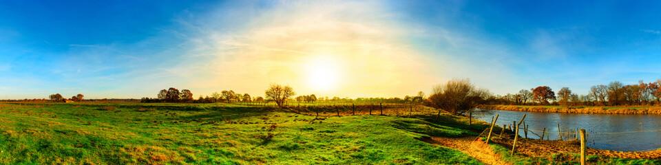 Fototapete - Landschaft im Herbst mit grünen Wiesen und Fluss bei Sonnenuntergang