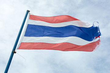 Wavy old flag of Thailand against blue sky