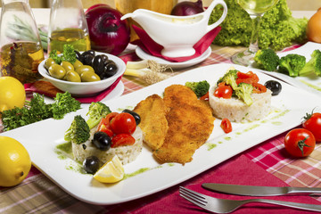 Portion, two pieces of deep fried fish rolled in bread crumbs and corn flour; side dish of boiled rice and broccoli; fresh cherry tomatoes, olives and lemon.