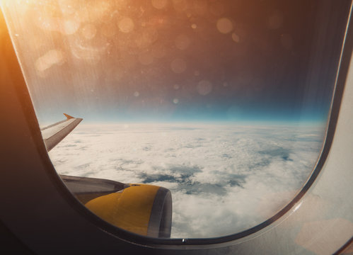 Beautiful wide view from window of aircraft: cloudscape, horizon, airplane wing and orange engine, flare and stylish lens dirt