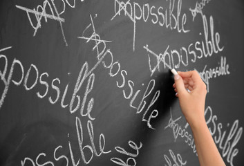 Female hand transforming IMPOSSIBLE into POSSIBLE on chalkboard