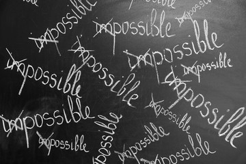Transformed IMPOSSIBLE words on chalkboard