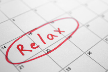 "Word ""relax"" written in day planner, close up view"
