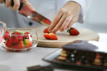 Cooking concept. Professional confectioner chopping strawberry on cutting board, closeup