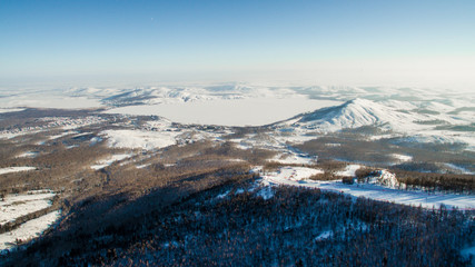 Russian Ural mountains in winter. Aerial view lake, white infinity