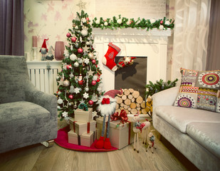 Christmas tree by the fireplace. Red stocking, gifts and decorations.
