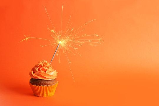 Fresh tasty cupcake with sparkler on orange background