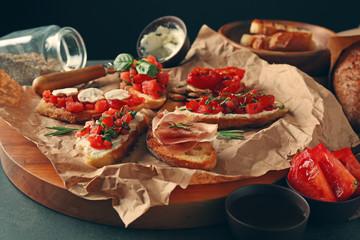 Tasty bruschetta on craft paper on wooden tray, closeup