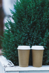 Two carton paper cups .on a wooden shelf at the Christmas tree