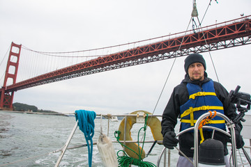 Man is holding steering wheel  on the sail boat in blue life vest. Bridge on background