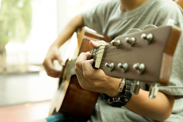 Asian teenager playing the acoustic guitar