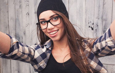 Hipster girl with braces. Wearing glasses and black beanie on the light wooden background