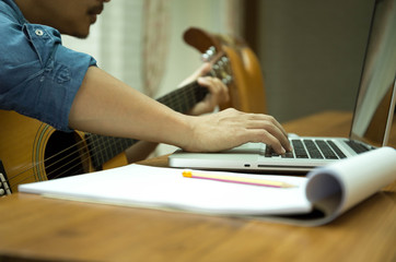 Man practicing play the guitar with laptop