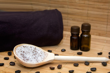 Spa concept.Coffee scrub, coffee beans, towel, aroma oil, candle on straw mat  background
