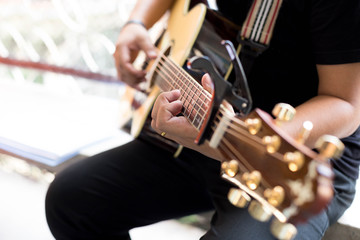 Man Practicing in playing acoustic guitar with a capo clip