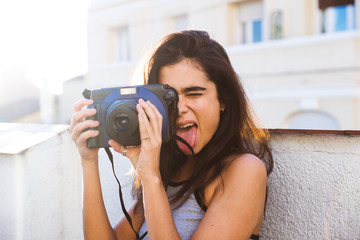 Woman with tongue out holding a camera