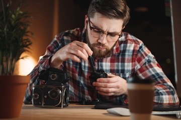 Portrait of a concentrated young man repairing an old camera