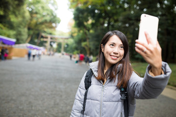 Woman taking selfie by mobile phone at Japanese temple