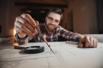 Smiling bearded man holding compass over graph