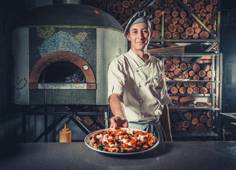 Young male cook holding fresh cooked pizza on white plate