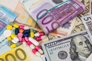 macro pills and tablets on euro and dollar banknotes for background.