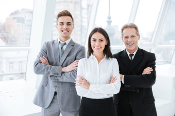 Three business people with arms crossed