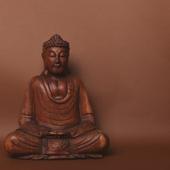 Wooden buddha statue against brown backgound