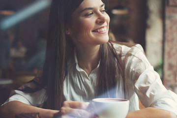 Cheerful woman with cup of coffee sitting in cafe and looking at the window. Bright sunny morning