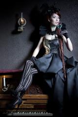Junge Frau im Burlesque Styling, auf einem Klavier sitzend, trink ein Glas Absinbth