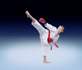 An athlete with a red belt strikes a high roundhouse kick