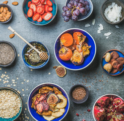 Ingredients for healthy breakfast in bowls over grey stone background, top view, square crop. Fresh and dried fruit, chia seeds, oatmeal, nuts, honey. Clean eating, vegan, detox, dieting concept