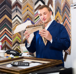 portrait of man seller working with picture frames in atelier