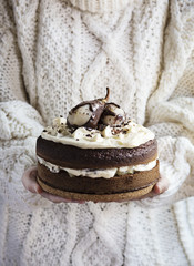 Woman's hands holding a chocolate cake