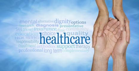 Healthcare Word Cloud - female hands gently cradling male hands on a pale misty blue vignette background with a healthcare word cloud to the left