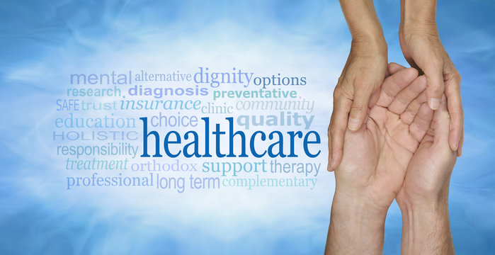 Healthcare Word Cloud - female hands gently cradling male hands on a pale misty blue vignette background with a healthcare word cloud to the left