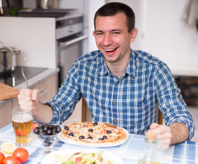 man eating pizza and salad in the kitchen at home