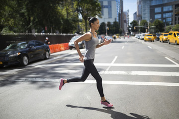 USA, New York City, woman running on urban street