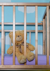 Toy in the crib. Conceptual image of a teddy bear in a child's cot