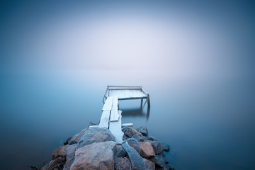 Frozen wooden pier on a blue foggy river and smooth reflection on water. Long exposure..