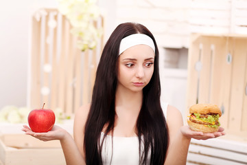 A young girl sits at home and makes a choice between healthy foo