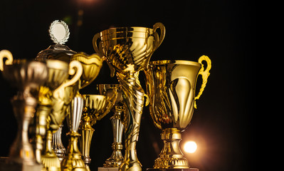 Group of the golden trophies in sparkling light on the dark background.