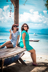Summer vacation, holidays, travel, friendship and people concept - two smiling young women on the beach of tropical island Nusa Lembongan, Indonesia, Asia. Sunny day, beautiful background. HDR photo.
