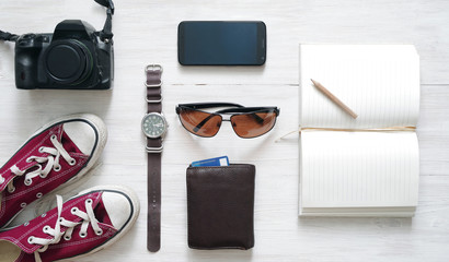 Preparation for a travel. Outfit of traveler, young woman or guy. Different objects on wooden surface, top view