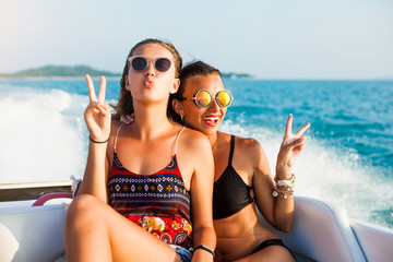 Two beautiful sexy happy hipster girl ride on a speed boat, the girls laugh and lifted up his hands, lifestyle, crazy emotions, glamor sunglasses, bikini, wet hair and skin, perfect bodies accessories