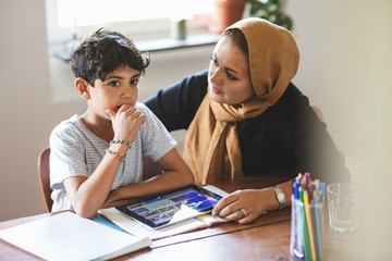 Mother looking at thoughtful son while studying at home